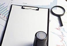 Skriv ut på tomt ett ark-, förstoringsglas- och diagramdokument arkivfoto