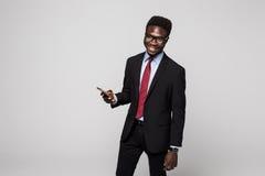 skriva ett meddelande Gladlynt svart manindräktmaskinskrivning något på mobiltelefonen och le, medan stå på grå färger royaltyfri foto