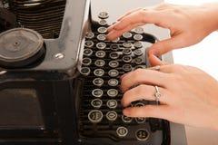 Skriva med den gamla svarta skrivmaskinen Royaltyfri Bild