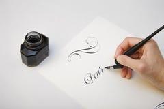 Skriva med fjäderpennan Spilld färgpulver- och reservoarpennabegreppsbild för att skriva process Tappningstiftpenna och bläckhorn Royaltyfri Foto