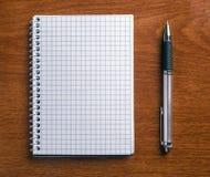 Skriva, och anteckningsboken på ett trä bordlägger. Royaltyfri Foto