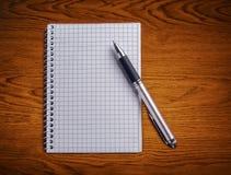 Skriva, och anteckningsboken på ett trä bordlägger. Arkivbild