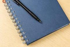 Skriva, och anteckningsboken på trä bordlägger Royaltyfri Fotografi