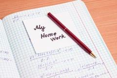 Skriva och ett stycke av papper med inskriften min läxa Arkivfoto