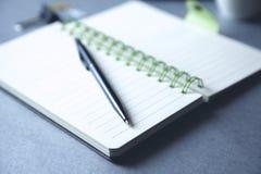 Skriva på anteckningsboken arkivbild