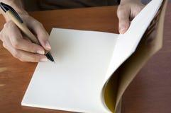 Skriva på anteckningsboken Fotografering för Bildbyråer