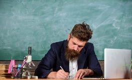 Skriva rapporten Läraren uppsökte manhandstil med pennan som var upptagen med skrivbordsarbete Lärare daglig rutinmässig skrivbor arkivfoton