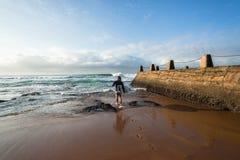 Skrivande in havvågor för surfare Arkivfoto