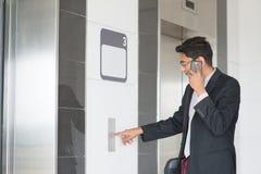 Skrivande in hiss för indisk affärsman Arkivfoton