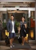 Skrivande in hotelllobby för lyckliga par Arkivbilder