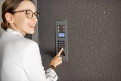 Skrivande in kod för kvinna på den byggande ingången arkivbild