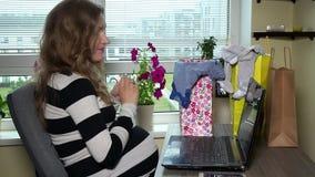 Skrivande in kreditkortdata för gravid kvinna på bärbar datordatoren arkivfilmer