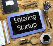 Skrivande in Startup handskrivet på den lilla svart tavlan 3d Arkivbild