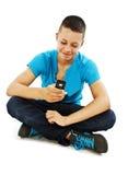 Skrivande textmeddelande för ung man på hans mobiltelefon arkivbild