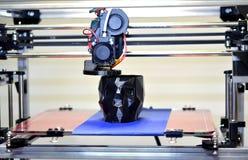 skrivare som 3D skrivar ut en modell i form av svart skallenärbild Arkivbild