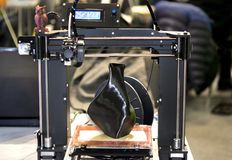 skrivare som 3D skrivar ut en modell i form av svart vasnärbild Arkivfoton