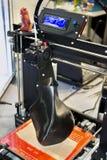 skrivare som 3D skrivar ut en modell i form av svart vasnärbild Royaltyfri Bild