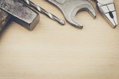 Skrivbord av ett trä med hammaren, drillborr, plattång, skiftnyckel Royaltyfri Foto