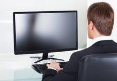 Skrivbord för affärsmanUsing Computer At kontor Arkivfoto