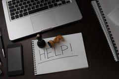 Skrivbord för bildogkontor eller kontorstabell med märkt HJÄLP och schackpjäser Royaltyfri Foto