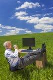 Skrivbord för fält för gräsplan för affärsmanRelaxing Drinking Coffee te Royaltyfri Fotografi