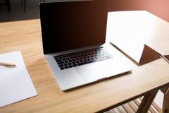 Skrivbord med översikten, den digitala minnestavlan och netto-boken i modernt kontor arkivfoton