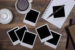 Skrivbord med anteckningsbok-, kaffe- och mellanrumspolaroidkameror Arkivfoto