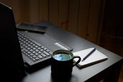 Skrivbord med bärbara datorn, den smarta telefonen, anteckningsböcker, pennor, glasögon och en kopp te Sidovinkelsikt royaltyfria bilder