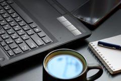 Skrivbord med bärbara datorn, den smarta telefonen, anteckningsböcker, pennor, glasögon och en kopp te Sidovinkelsikt arkivfoto