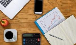 Skrivbord med datoren och finansiell utrustning som analyserar financi Fotografering för Bildbyråer