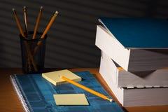 Skrivbord med den självhäftande anmärkningen i natt Arkivfoto