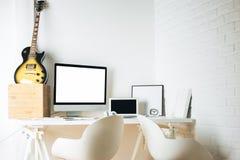 Skrivbord med den tomma apparater och gitarren Royaltyfri Bild