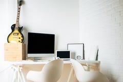 Skrivbord med den tomma grejer och gitarren Royaltyfria Bilder
