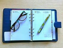 Skrivbord med exponeringsglas, dagboken och blyertspennan Royaltyfri Fotografi