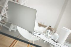 Skrivbord med kaffe och hörlurar Royaltyfria Foton