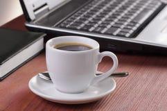 Skrivbord med kaffekoppen, den öppnade bärbar datordatoren och dagboken på bakgrund, inga personer som fokuseras på kaffe Arkivbild