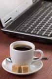 Skrivbord med kaffekoppen och den öppnade bärbar datordatoren, inga personer som fokuseras på kaffe Royaltyfri Bild