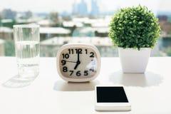 Skrivbord med klockan och telefonen Arkivfoton