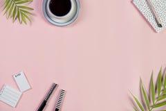 Skrivbord med koppen kaffe, notepaden, bråklistan och pennor på ett ljus - rosa bakgrund Top beskådar arkivbilder