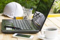 Skrivbord med nivån och utrustning för arkitekt på trätabellen med utomhus- sikt bredvid arkivfoton