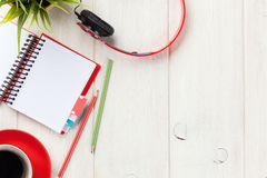 Skrivbord med notepaden, kaffe och hörlurar Arkivfoto