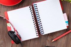 Skrivbord med notepaden, kaffe och hörlurar Arkivbilder