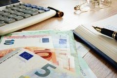 Skrivbord med revisorboken, eurosedlar och räknemaskinen rikedom royaltyfria foton