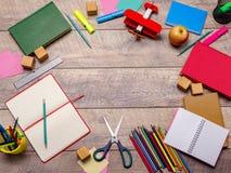 Skrivbord med skolatillförsel mot träbakgrund Arkivbild