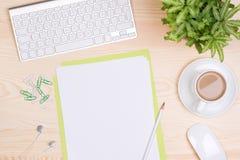 Skrivbord med tangentbordet, brevpapper och en kopp kaffe Arkivbild