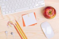 Skrivbord med tangentbordet, brevpapper och ett äpple Royaltyfri Foto