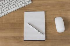 Skrivbord med tangentbordet och notepaden Royaltyfria Bilder