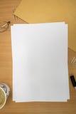 Skrivbord med tomt papper arkivfoto