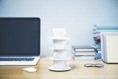 Skrivbord med tornet för kaffekopp Arkivfoto
