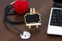 Skrivbordet för doktors` s med bärbara datorn, stetoskop och röd hjärta och bla Fotografering för Bildbyråer